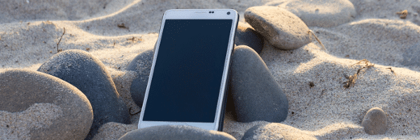 Phone in Sand and Rocks at the Beach